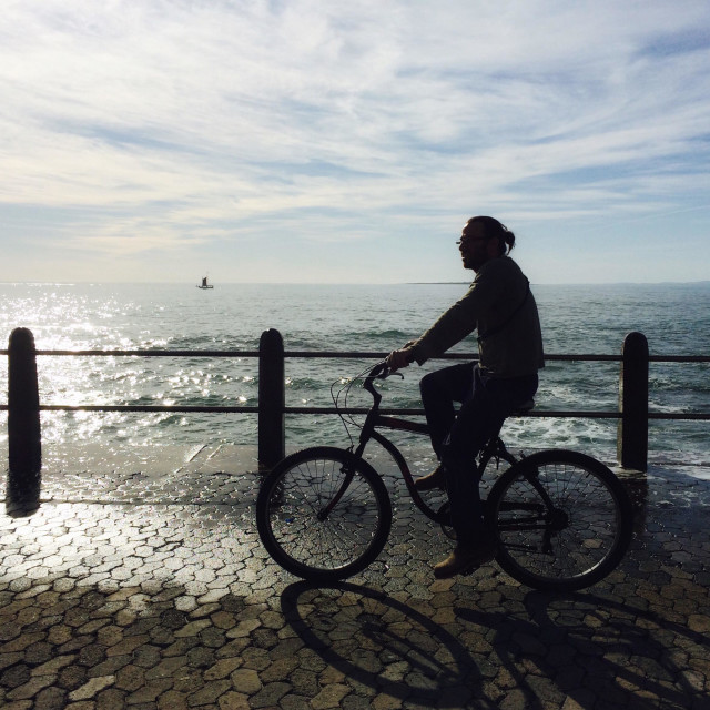 """""""Man cycling along Seapoint promenade, South Africa."""" stock image"""