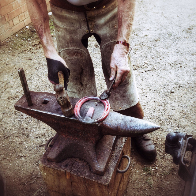 """""""Blacksmith with a heated horseshoe and anvil"""" stock image"""