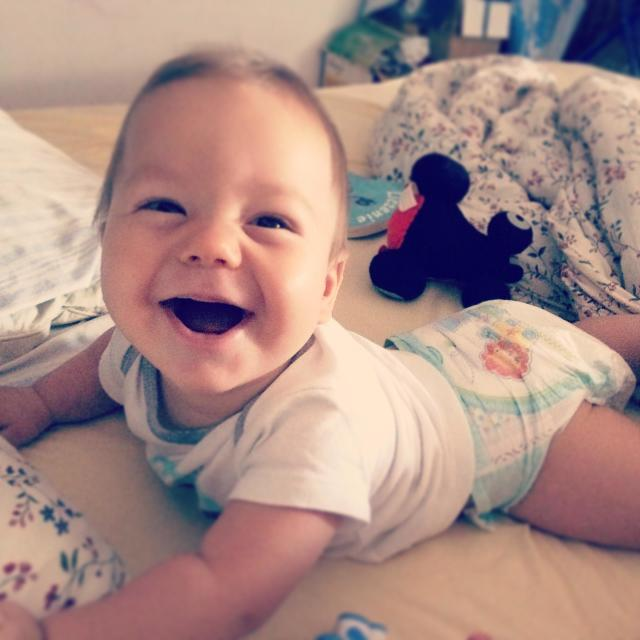 """""""Baby boy smiling lying on his tummy on his parent's bed"""" stock image"""