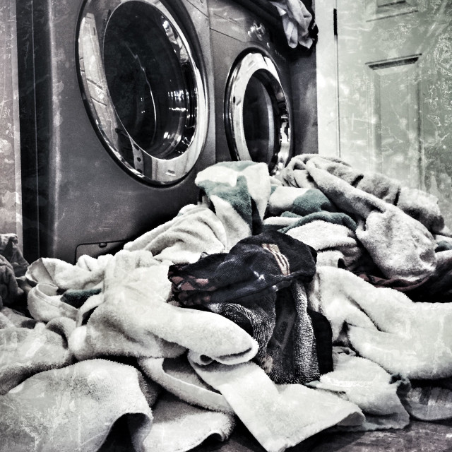 """A daunting scene of piled up laundry in front of washing machine and dryer duo."" stock image"