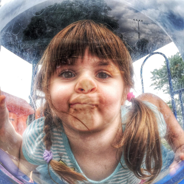 """Toddler girl on playground being silly"" stock image"