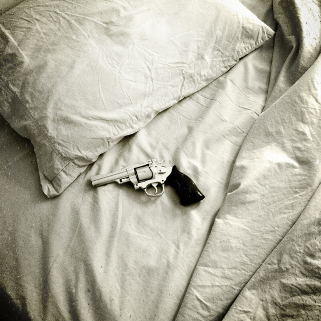 """Handgun on a bed."" stock image"