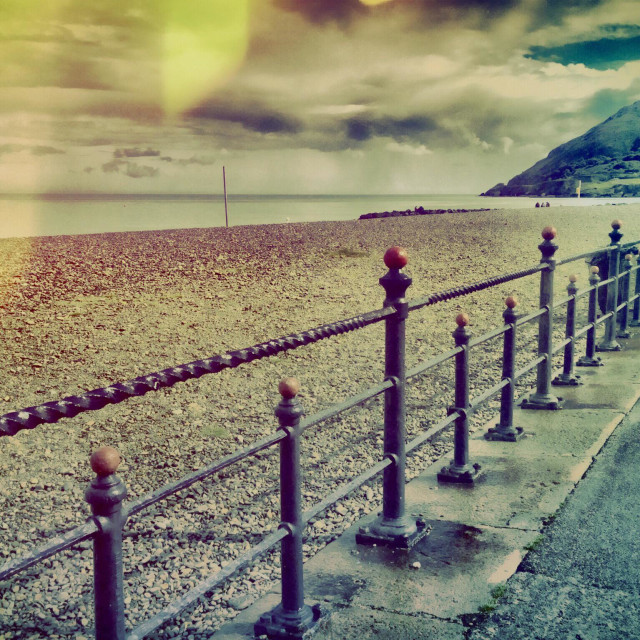 """Railings along shingle beach with light leak lead towards hilltop"" stock image"