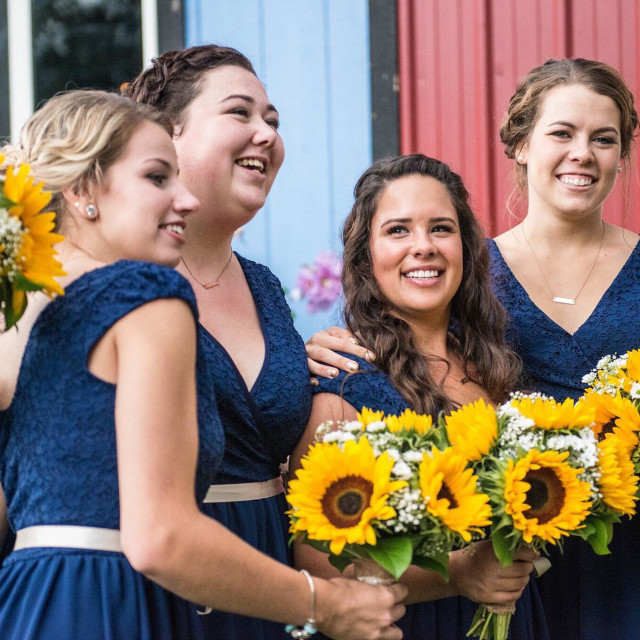 """""""4 bridesmaids at a county wedding with navy blue dresses that match and holding sunflower bouquets"""" stock image"""