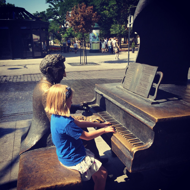 """""""Little girl sitting next to the statue of a famous polish composer Moniuszko, on Piotrkowska street in Lódz, Poland, pretending to play his grand piano alongside him"""" stock image"""