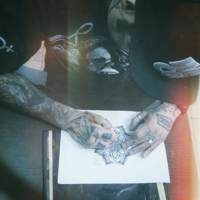 """""""Tattoo artist tracing contours of mandala sketch on transfer paper"""" stock image"""