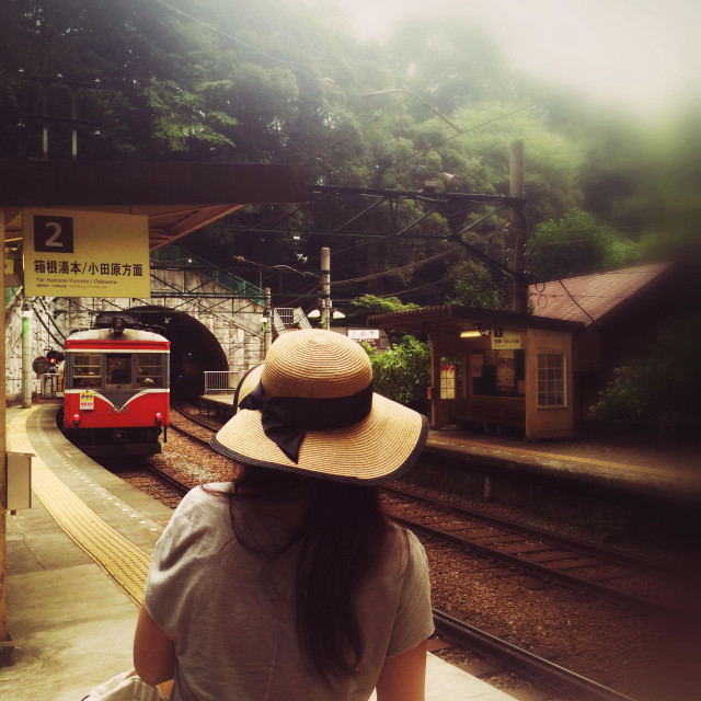 """""""Japanese lady with straw hat waits at mountain railway station as train arrives out of tunnel"""" stock image"""
