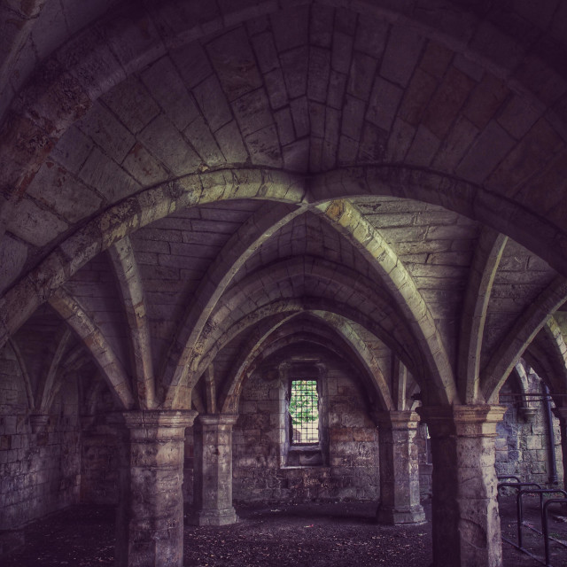 """Dark and gloomy church catacombs with a single, barred window and dimly lit arches."" stock image"