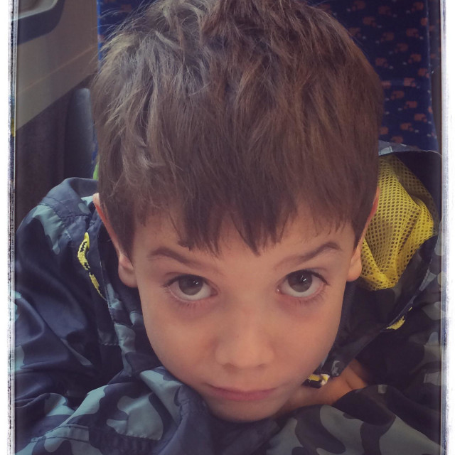 """Close up shot of a boy on a train sad to leave his holiday in Sudbury, Suffolk"" stock image"