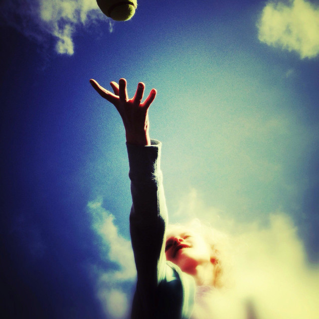 """""""Young girl reaching out to catch tennis ball"""" stock image"""