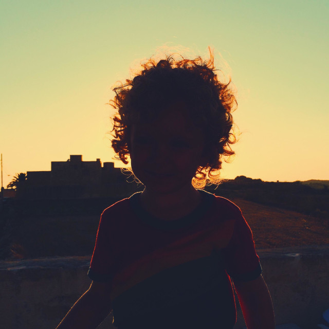 """Glowing silhouette of boy with sun going down in background"" stock image"