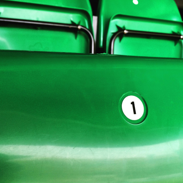 """""""Number One on a folding green chair in the grandstand at a sports stadium."""" stock image"""