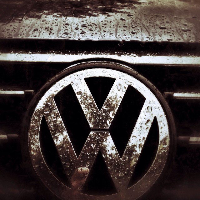 """VW logo on the front of the car wet with rain"" stock image"