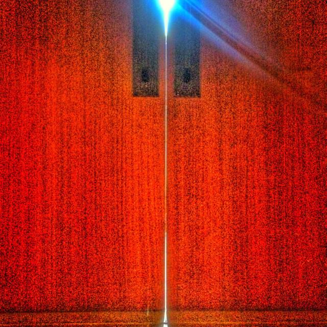 """Red door with light peeking through"" stock image"