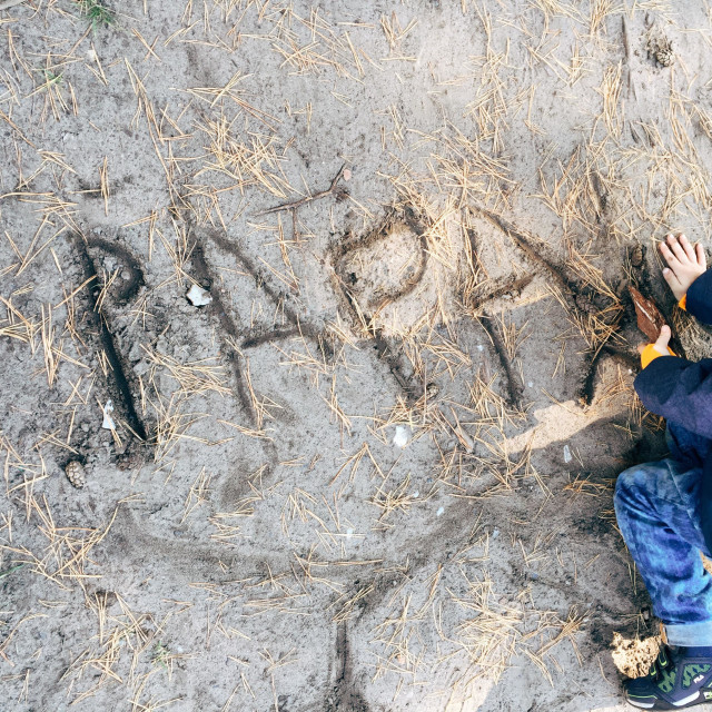 """""""Young boy writing Papa with a stick into the sand"""" stock image"""