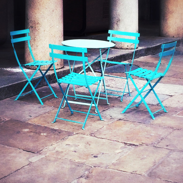 """""""Cafe table and four chairs by stone pillars."""" stock image"""