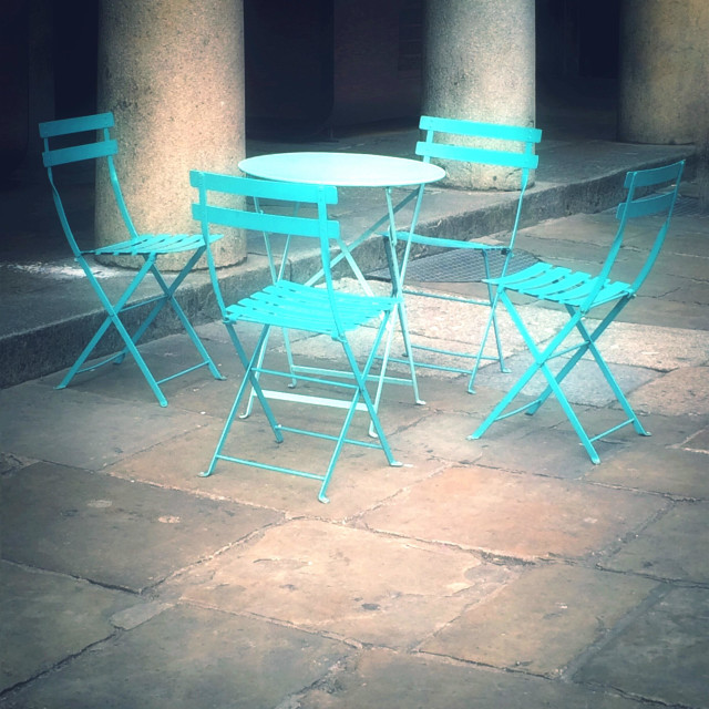 """""""Four brightly coloured blue chairs and a table in a courtyard setting."""" stock image"""