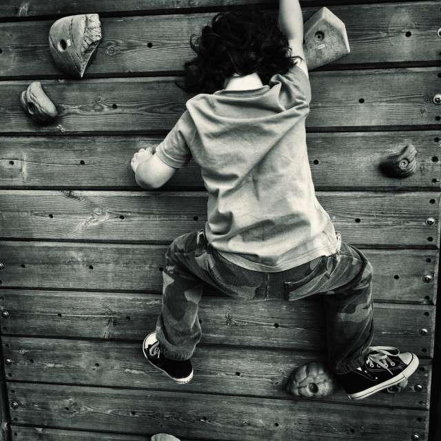 """Young boy four years on climbing wall"" stock image"