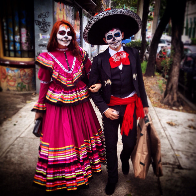 """A couple of Mexicans dressed with traditional costumes for Day of the Dead celebrations walk in a street of Colonia Roma, Mexico City, Mexico"" stock image"