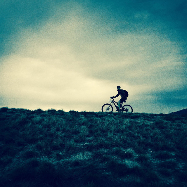 """""""The silhouette of a man riding a mountain bike up the hill in northern Utah."""" stock image"""