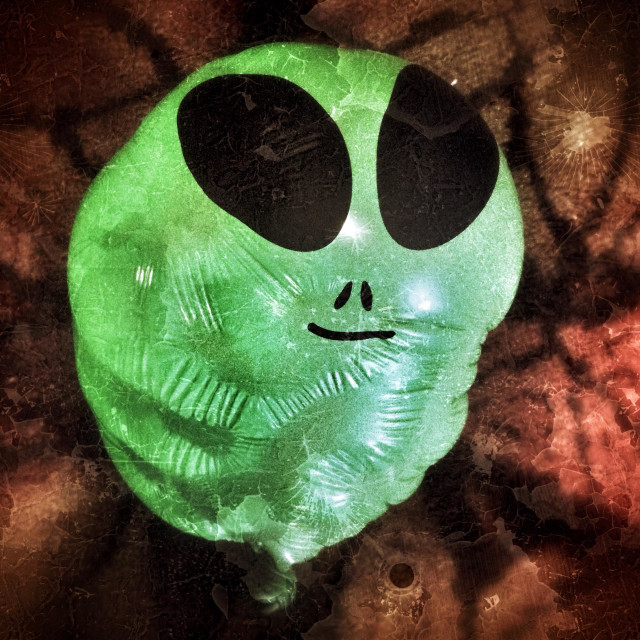 """""""Partially deflated balloon with an alien face on a grunge background"""" stock image"""