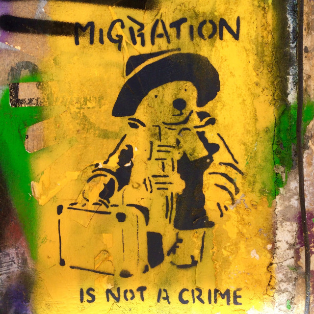 """""""Timely and political Paddington Bear street art in Athens, Greece, with the message 'Migration is not a crime'."""" stock image"""