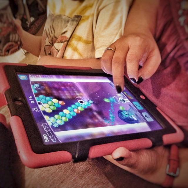"""""""Woman playing a game on an iPad."""" stock image"""