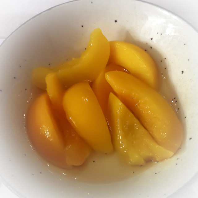 """""""Canned peaches in dessert bowl"""" stock image"""