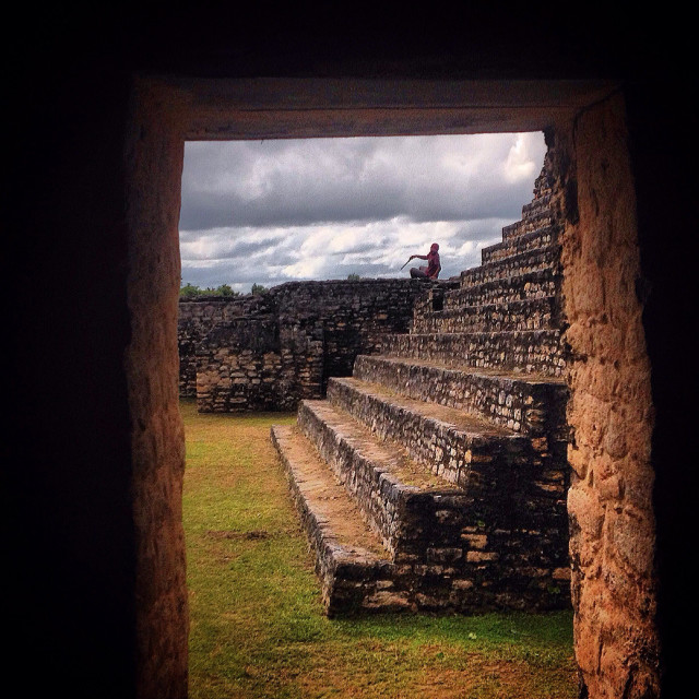 """""""A person sits in the remains of the Mayan city of Caracol in Cayo, Belize"""" stock image"""