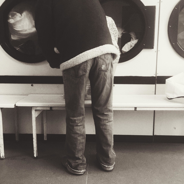 """""""A man putting washing in a dryer in a launderette"""" stock image"""