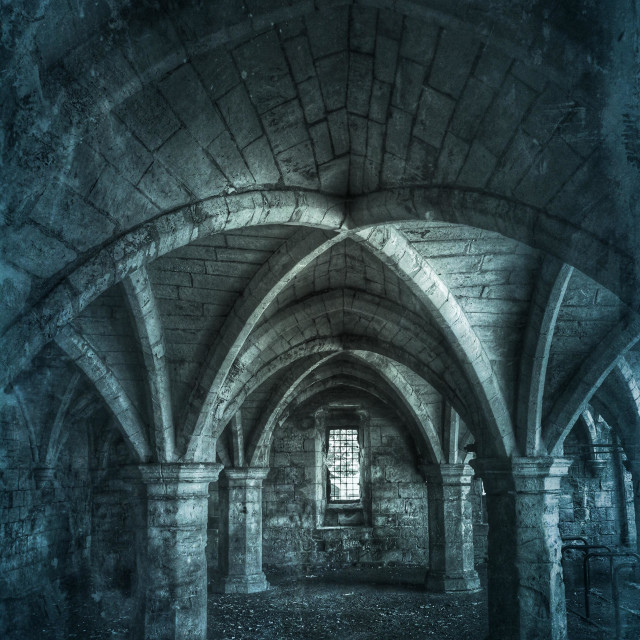 """Cold, underground catacombs with ornate arches and a single, barred window throwing light into the room."" stock image"