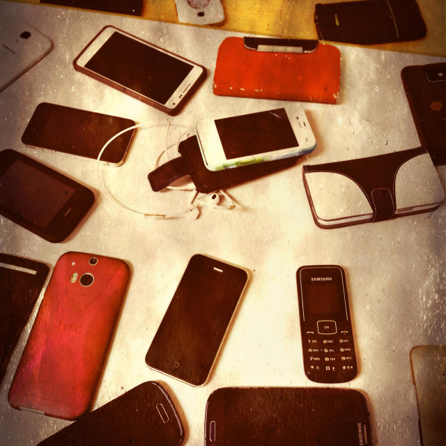 """Smartphones and cellphones on a table during an exam to prevent cheating"" stock image"