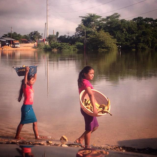 """Two Mayan girls carry fruit in the river cross of Sayaxche, Peten, Guatemala"" stock image"