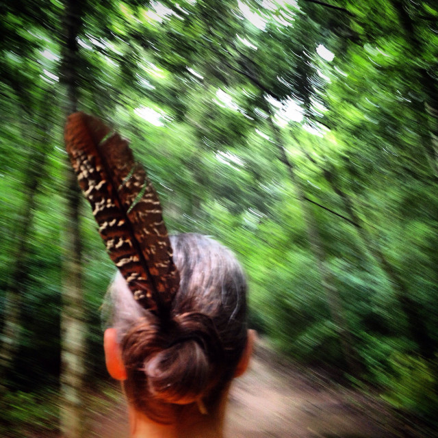 """""""A woman wearing a bird feather walks in the jungle in the Mayan city of Mirador, Peten, Guatemala"""" stock image"""