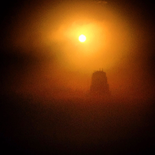 """""""The sun shines at sunrise in the morning fog in the Mayan city of Tikal, Peten, Guatemala"""" stock image"""