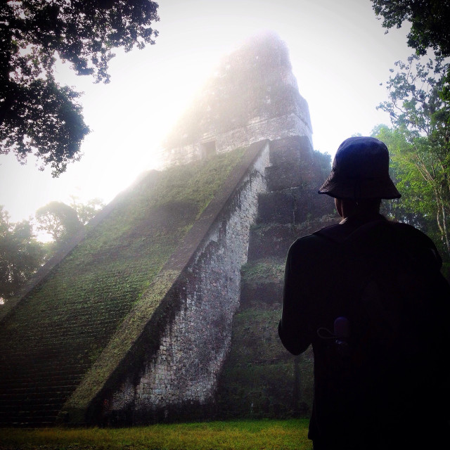 """""""A tourist looks at a temple covered by fog in the Mayan city of Tikal, Peten, Guatemala"""" stock image"""