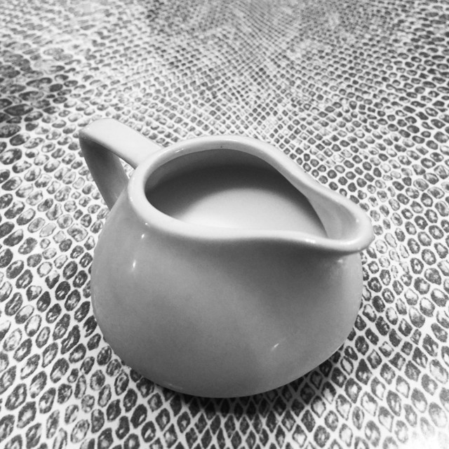 """Milk jug on snake skin pattern table"" stock image"