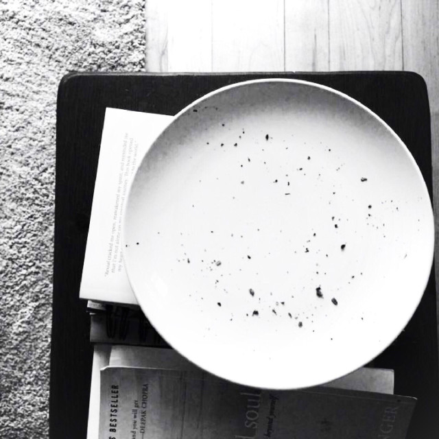 """Black and white of an empty plate with toast crumbs sitting on a bench"" stock image"