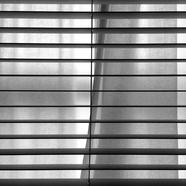"""""""A venetian blind and pale linen curtains over a window."""" stock image"""