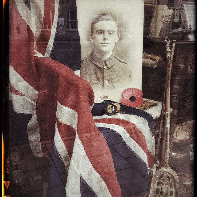 """""""A window display to commemorate Armistance Day, 11th November. The Union Jack Flag is draped over a chair and next to a red poppy, war medals and a photographic portrait of a young soldier."""" stock image"""