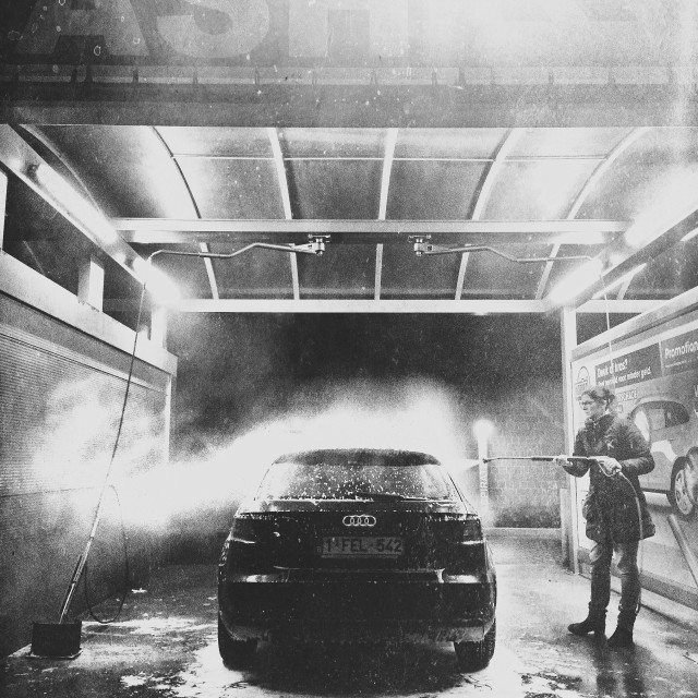 """""""Woman cleaning her car in a self service car wash during the evening"""" stock image"""