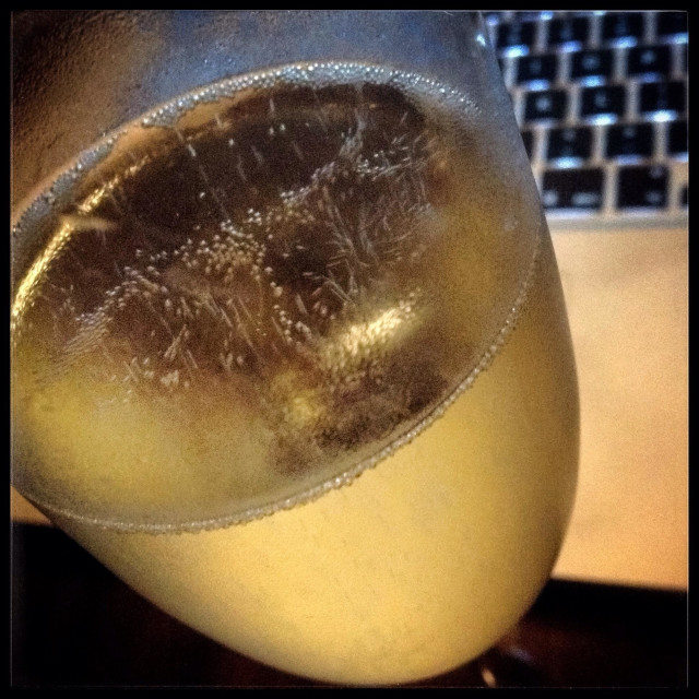 """A glass of Cava sparkling wine with a computer in the background."" stock image"