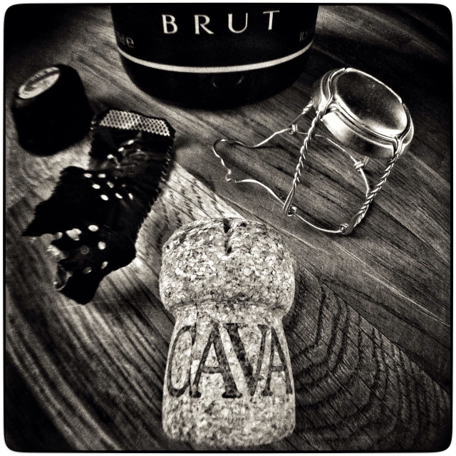 """Spanish Cava sparkling wine cork with bottle on a wooden table."" stock image"