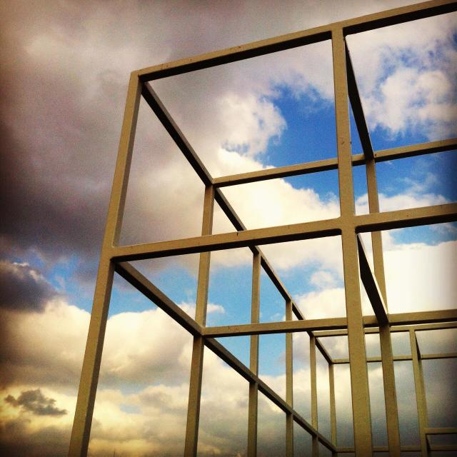 """""""Metal frame (jungle gym) against clouds"""" stock image"""