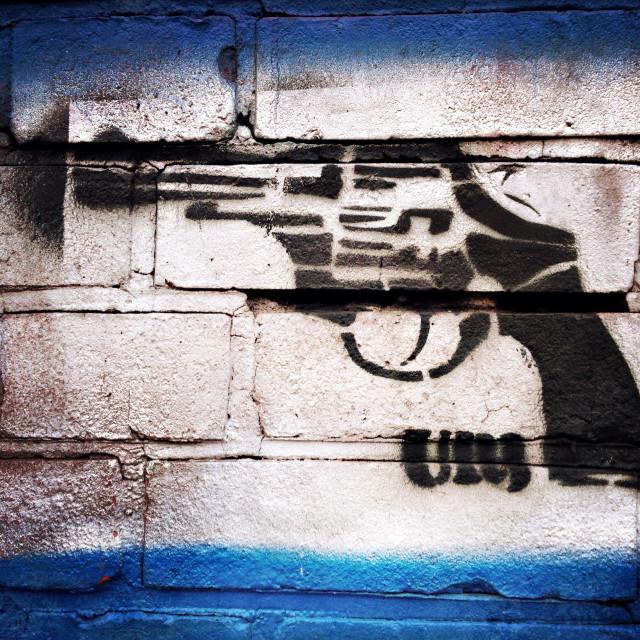 """A stencil graffiti of a revolver on a brick wall in Berlin, Germany"" stock image"