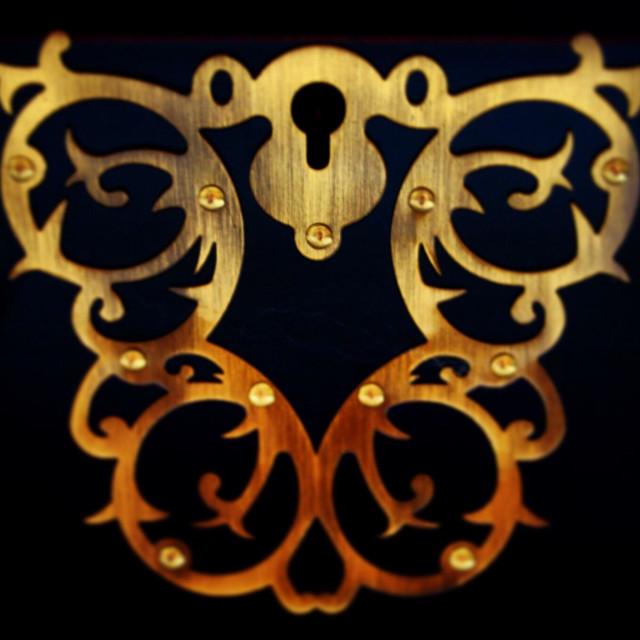 """Gilded keyhole decoration on a mahogany jewelry box."" stock image"