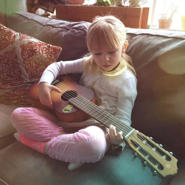 """Mini Joni- girl practicing guitar in living room while sun streams in through bay window"" stock image"