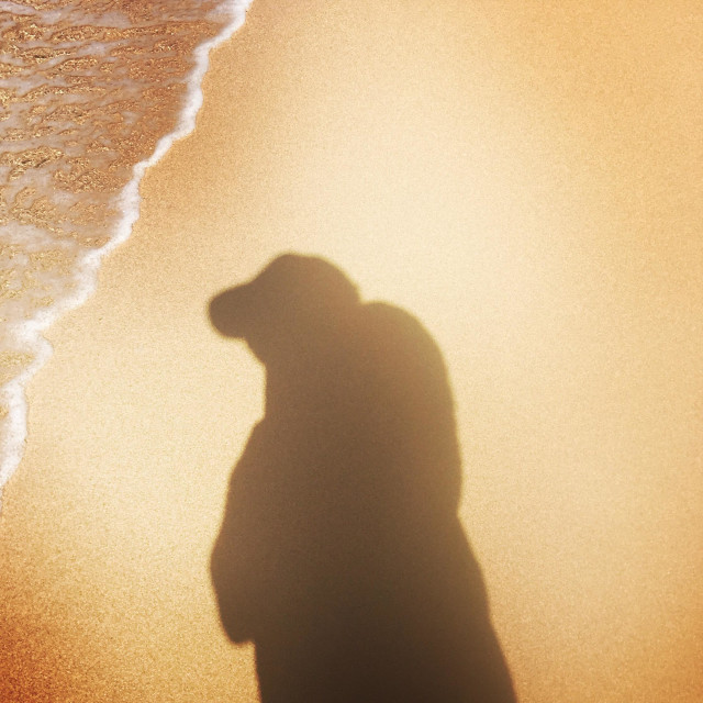 """""""A shadow of a male at the waterline at the beach. Hanalei, Kauai, Hawaii USA."""" stock image"""