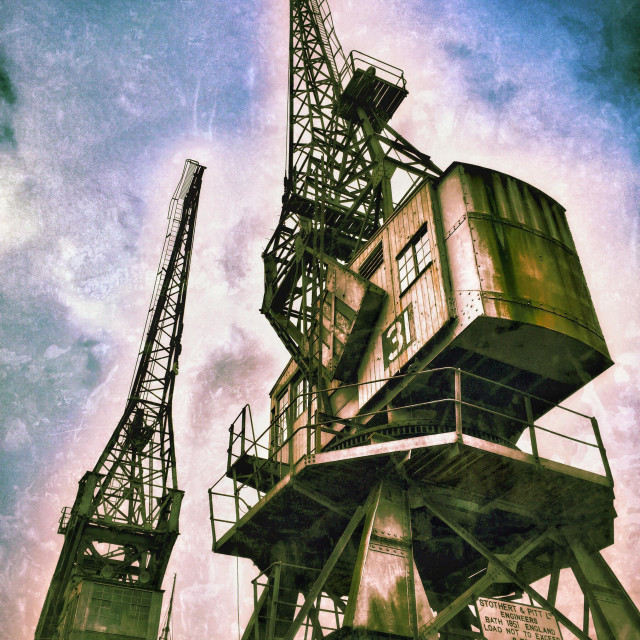 """""""Two of the Large Cranes situated on the edge of The Floating Harbour, close to the City Centre of Bristol, England. The Cranes were used to offload cargo from ships. Photo Credit - © COLIN HOSKINS."""" stock image"""