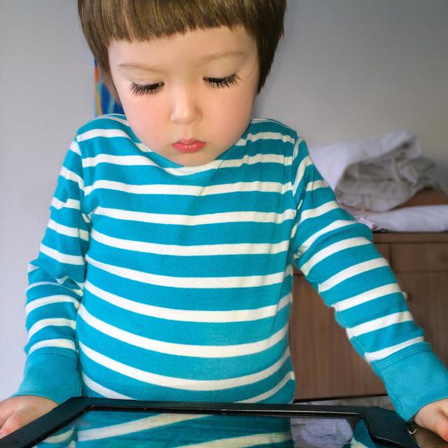 """A young boy looking at an iPad"" stock image"